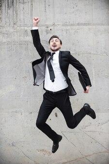 Groot succes. gelukkige jonge man in formele kleding die zijn armen omhoog houdt en positiviteit uitdrukt terwijl hij voor de betonnen muur springt