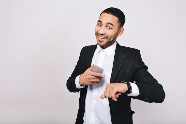 Groot succes, goede resultaten als in carrière van knappe jongeman in wit overhemd, zwarte jas lachend met telefoon. stijlvolle zakenman, glimlachend.