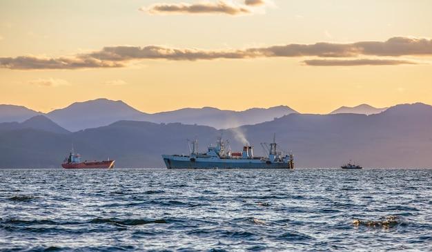 Groot vissersvaartuig op de achtergrond van heuvels en vulkanen op het schiereiland kamtsjatka