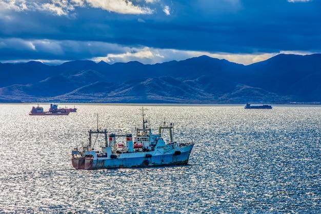 Groot vissersvaartuig op de achtergrond van heuvels en vulkanen selectieve focus