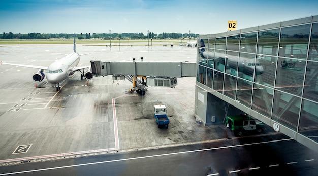 Groot vliegtuig geparkeerd naast boarding gate in luchthaventerminal