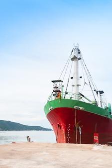 Groot vrachtschip met vele verschepende container in haven