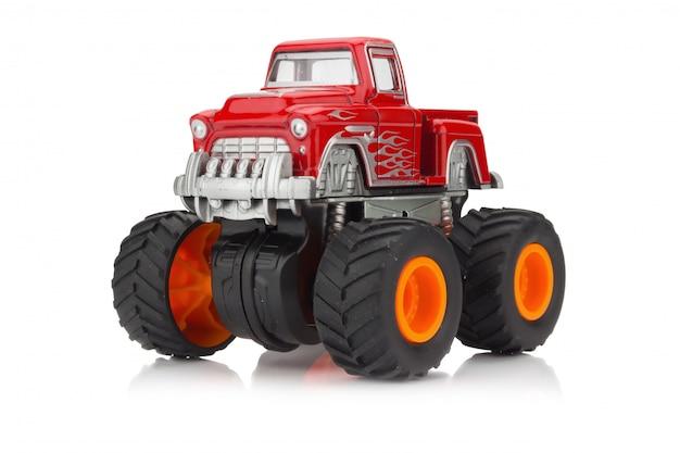 Groot vrachtwagenstuk speelgoed kleurenrood dat op witte achtergrond wordt geïsoleerd