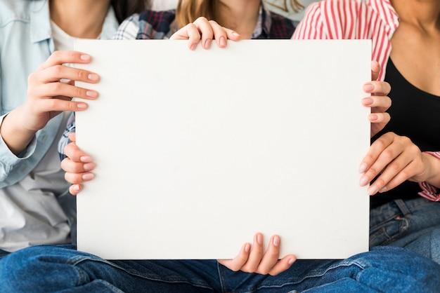 Groot wit blad van papier dat door vrouwen houdt