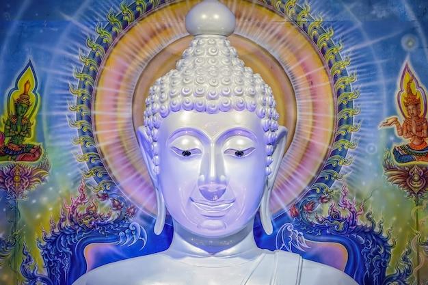 Groot wit boeddhabeeld met blauwe muur als achtergrond.