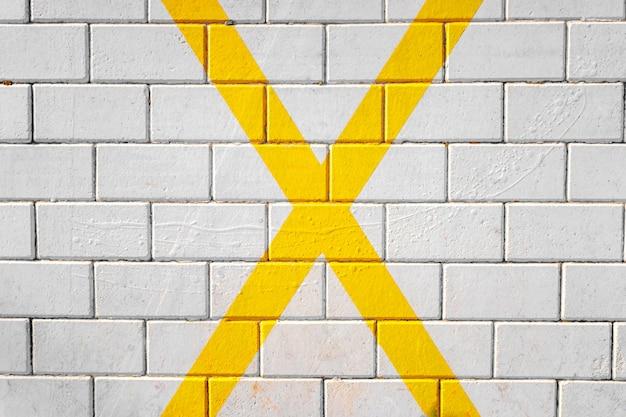 Groot x-vormig geel kruis geschilderd op de stoep, achtergrond van een parkeerplaats.