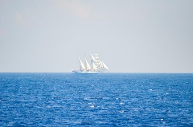 Groot zeilschip vaart aan de horizon. (santorini)