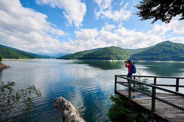 Grootheid van de natuur. jonge vrouwelijke fotograaf maakt foto van geweldig meer en groene rotsachtige bergen