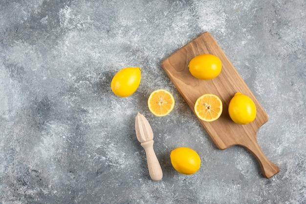 Groothoek foto van stapel citroenen op houten bord en grond.