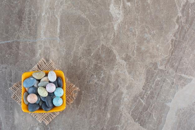 Groothoek foto van stenen snoepjes in kom over grijze achtergrond.