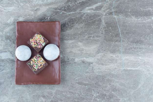Groothoek foto van zelfgemaakte koekjes met wafel op bruine plaat.