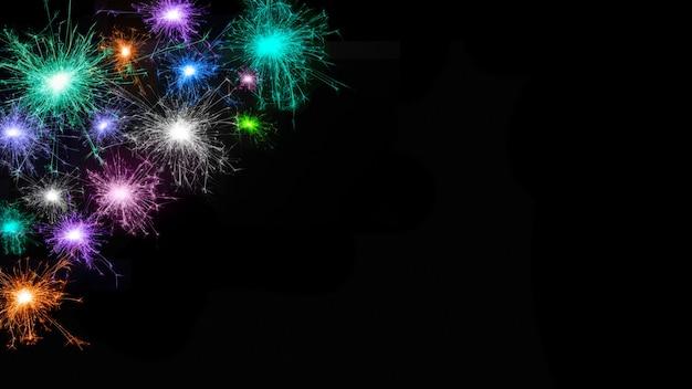 Groothoek mooie vuurwerk achtergrond. frame van veel veelkleurige vuurwerk geïsoleerd op zwarte achtergrond. sjabloon voor ontwerp: kerstmis, nieuwjaar, jubileum, verjaardag