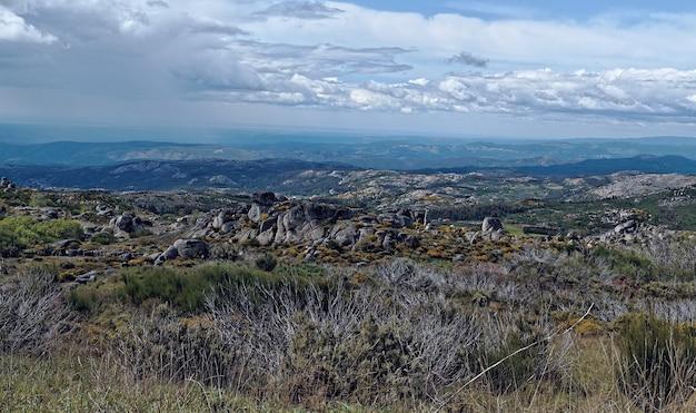 Groothoek opname van een groot rotsachtig en grasrijk veld met wolken aan de hemel