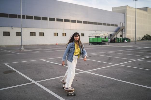 Groothoek opname van een meisje op een skateboard achter een gebouw