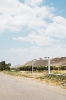 Groothoek opname van een metalen pijp passeren rond een weg voor een berg onder een bewolkte hemel