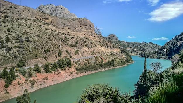 Groothoek opname van een rivier die overdag naast de bergen stroomt
