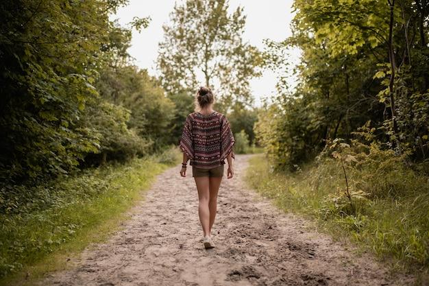 Groothoek opname van een vrouw die door een wandelpad loopt, omringd door bomen