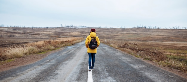 Groothoek opname van een vrouwelijke toerist met een rugzak die gele jas en rode hoed draagt, loopt op de weg.