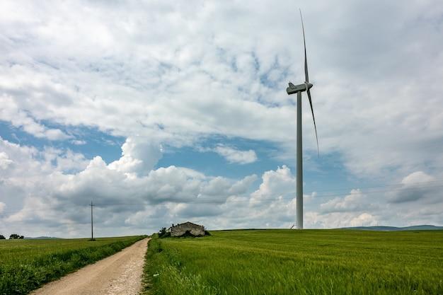 Groothoek opname van een windventilator naast een groen veld onder een bewolkte hemel