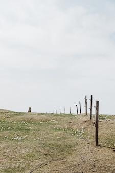 Groothoek opname van groen gras onder een bewolkte hemel, omgeven door een houten hek