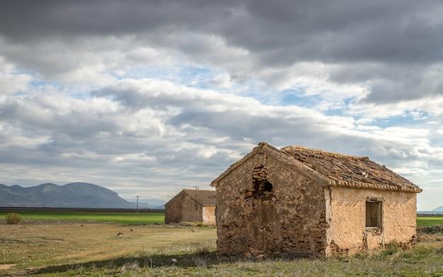 Groothoek opname van oude huizen op een groen veld onder een bewolkte hemel