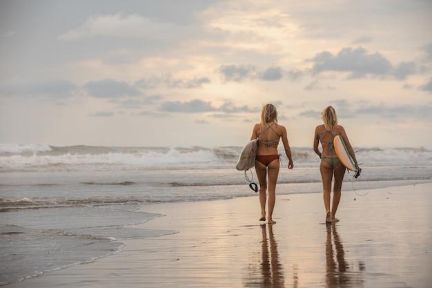 Groothoek opname van twee meisjes met surfplanken wandelen op het strand