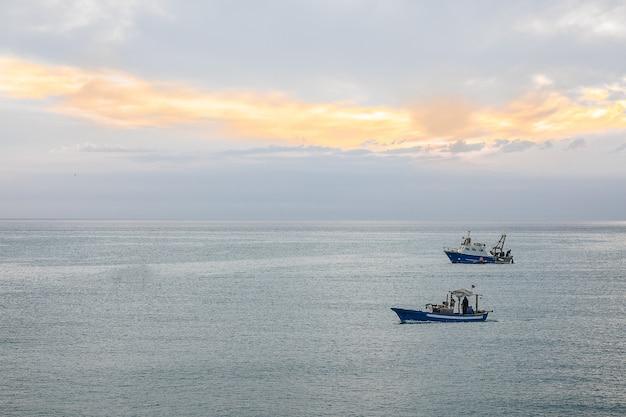 Groothoek opname van twee schepen die onder een bewolkte hemel over de oceaan varen