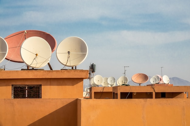 Groothoek opname van witte satellietschotels op het dak van een gebouw