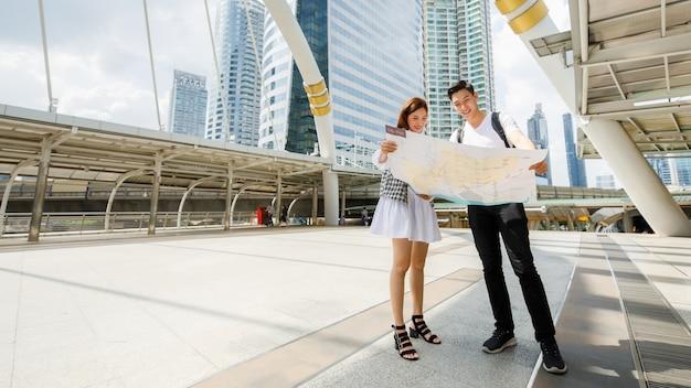 Groothoek portret schattige lachende jonge aziatische minnaar reizigers staan en houden een papieren stadsplattegrond op voetgangersbrug samen om richting te vinden naar bestemmingen met hoog gebouw en hemelachtergrond