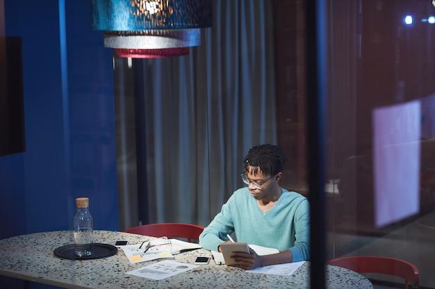Groothoek portret van jonge afrikaanse zakenman laat werken zittend aan tafel in een donkere kamer en met behulp van digitale tablet
