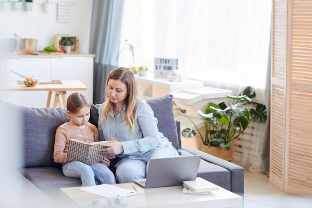 Groothoek portret van liefdevolle volwassen moeder kijken schattig meisje boek lezen of studeren zittend op de bank in gezellig interieur, kopie ruimte
