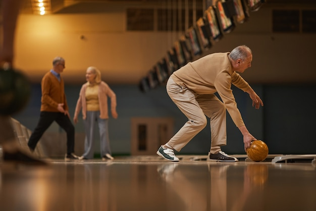 Groothoek zijaanzicht bij senior paar man bowlen terwijl u geniet van actief entertainment op bowlingbaan, kopieer ruimte