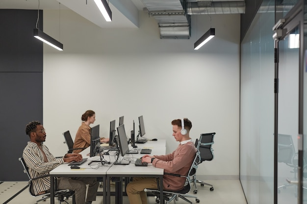 Groothoekbeeld bij groep studenten die computers gebruiken in de schoolbibliotheek of het it-lab, kopieer ruimte