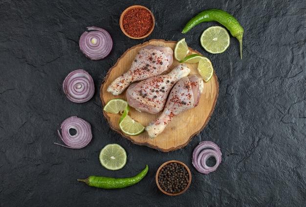 Groothoekfoto van rauwe kip drumsticks en groenten op een houten bord.