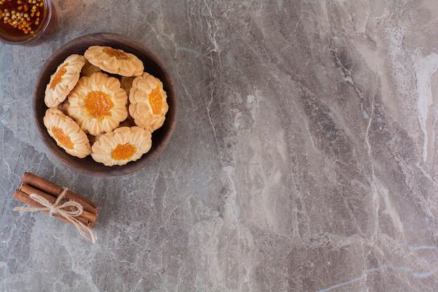 Groothoekfoto van zelfgemaakte jam koekjes in een houten kom over grijs.
