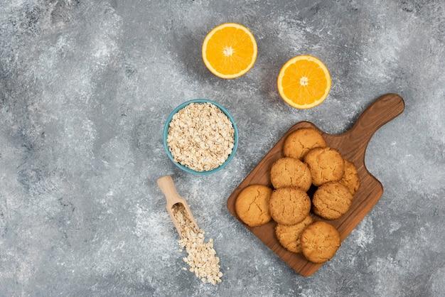 Groothoekfoto van zelfgemaakte koekjes op een houten bord en havermout met sinaasappels over grijs oppervlak