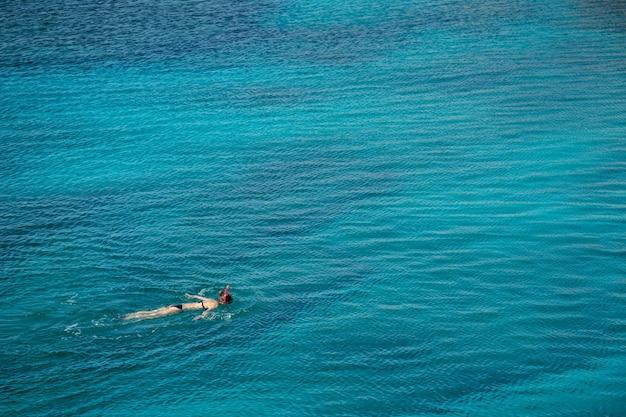 Groothoekopname van een persoon die in het water zwemt