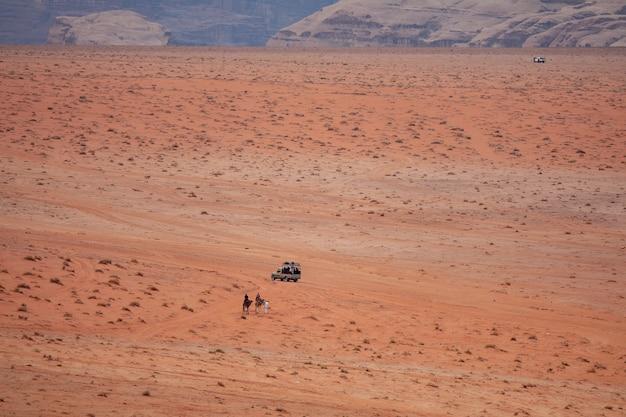 Groothoekopname van twee mensen op kamelen die een auto in een woestijn naderen