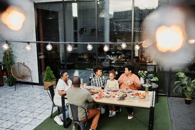 Groothoekportret van een grote afro-amerikaanse familie die aan tafel zit en samen geniet van het diner...