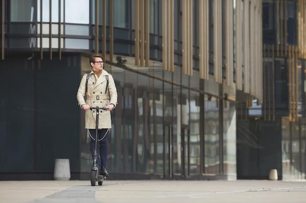 Groothoekportret van moderne jonge zakenman die elektrische autoped naar camera berijdt tijdens het pendelen om met stedelijke stadsgebouwen op achtergrond te werken, exemplaarruimte