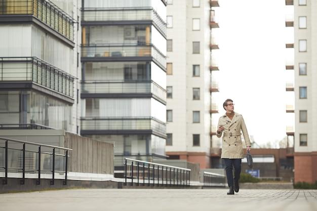 Groothoekportret van moderne jonge zakenman die trenchcoat draagt die naar camera loopt tijdens het pendelen om te werken in stedelijke stadsomgeving, exemplaarruimte