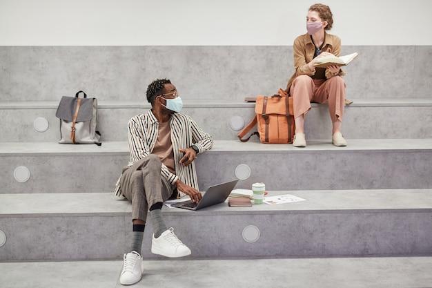 Groothoekportret van twee jonge studenten die werken en ontspannen terwijl ze in de grafische universiteitslounge zitten, kopieer ruimte