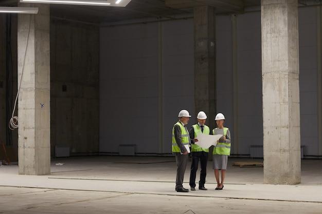 Groothoekportret van zakenmensen die hardhats dragen en plannen houden terwijl ze op de bouwplaats binnenshuis staan,