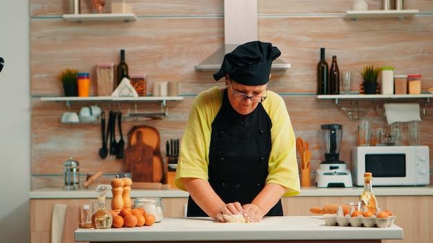 Grootmoeder bereidt tarwe zelfgebakken brood met chef-kok bonete. gepensioneerde bejaarde bakker met bonete die ingrediënten mengt met tarwebloem die deeg kneedt voor het bakken van zelfgemaakte cake en brood