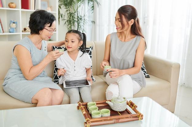 Grootmoeder blaast op warme drank voordat ze het aan kleine kleindochter geeft die op de bank zit met een digitale tablet