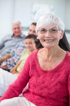 Grootmoeder die camera en het glimlachen bekijkt