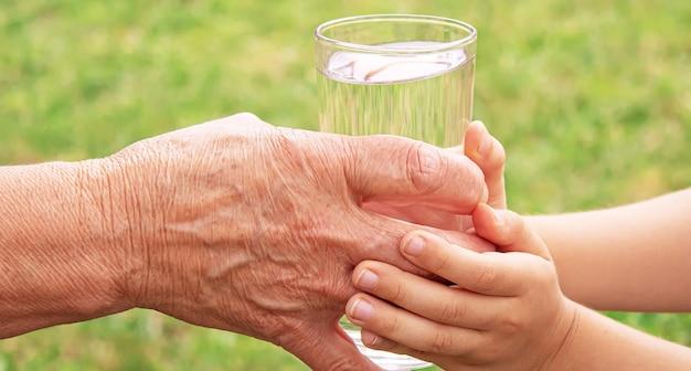 Grootmoeder die een glas schoon water geeft aan een kind. selectieve aandacht. natuur.