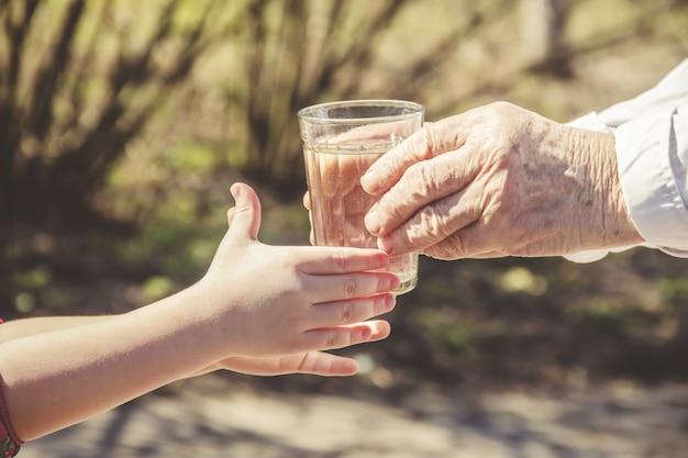 Grootmoeder die een glas schoon water geeft aan een kind. selectieve aandacht.