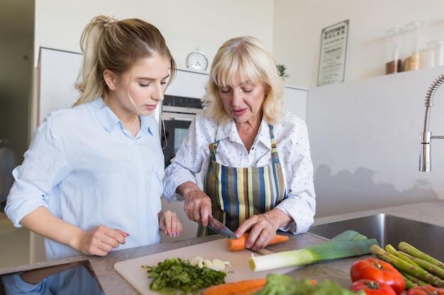 Grootmoeder die haar kleindochter leert hoe ze een salade moet maken