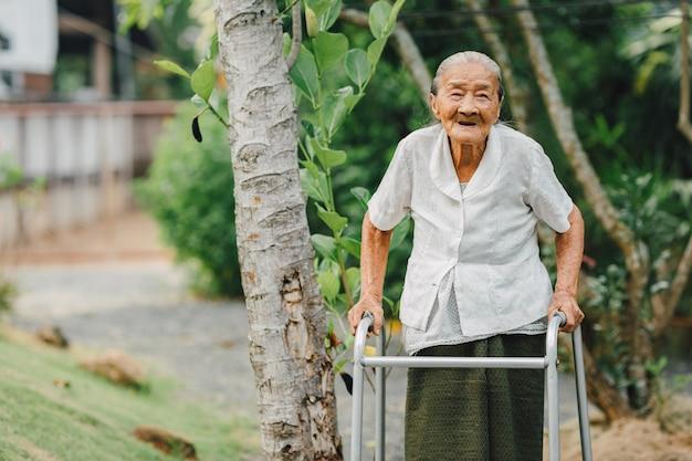 Grootmoeder die met leurder in de tuin loopt
